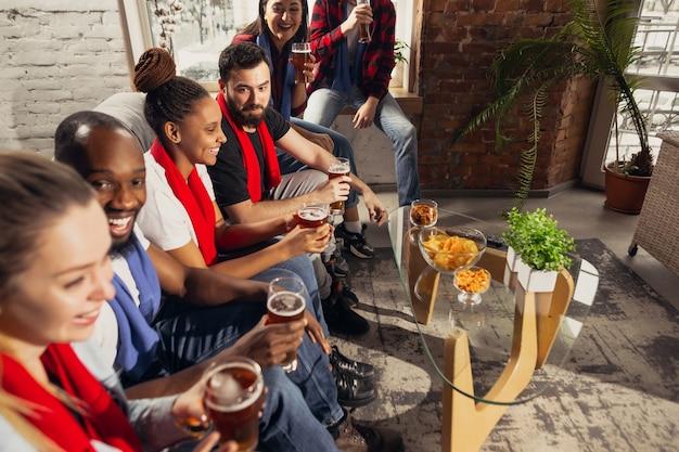 Podekscytowana grupa ludzi oglądająca piłkę nożną, mecz sportowy w domu