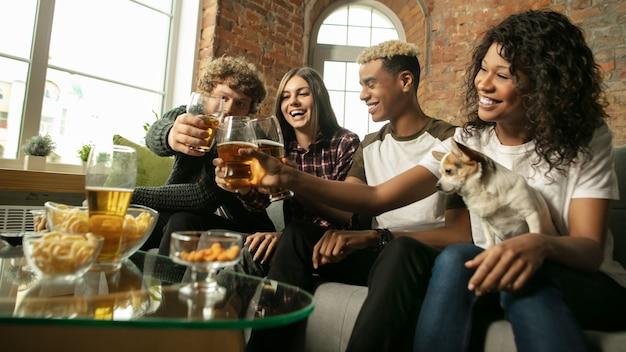 Podekscytowana grupa ludzi oglądająca w domu mistrzostwa meczów sportowych