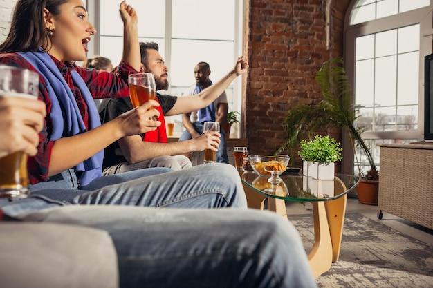 Podekscytowana grupa ludzi oglądających mecz piłki nożnej w domu
