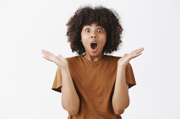 Podekscytowana i pod wrażeniem przystojna stylowa młoda afroamerykanka w brązowej koszulce dysząca i opadająca szczęka ze zdumienia i zaskoczenia klaszcząca w dłonie zdumiona