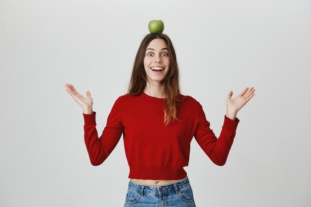 Podekscytowana i rozbawiona dziewczyna uśmiechnięta, trzymając jabłko na głowie cel lub cel