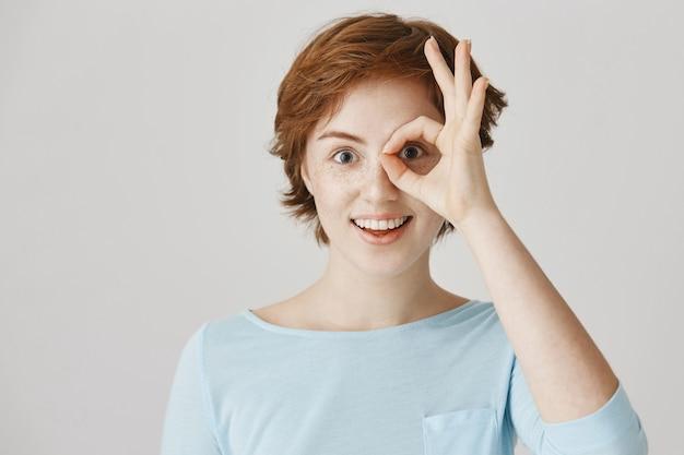 Podekscytowana i rozbawiona ruda dziewczyna pozuje przy białej ścianie