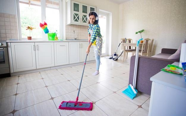 Podekscytowana i szczęśliwa piękna młoda kobieta w fartuchu czyści podłogę w swojej kuchni w domu i tańczy