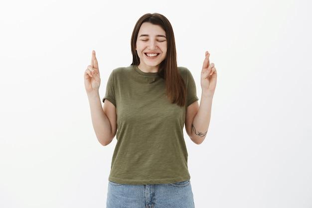 Podekscytowana i urocza szczera młoda dziewczyna z tattto pochyloną w podekscytowaniu i szczęściu, z zamkniętymi oczami i szczęśliwym uśmiechem, kciuki na szczęście, życzenia, modląc się o spełnienie marzeń na szarej ścianie