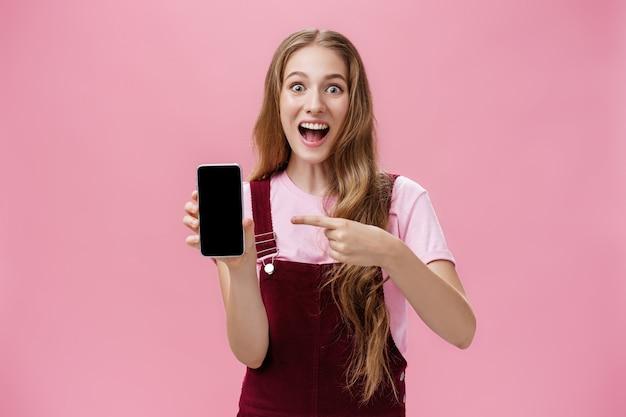 Podekscytowana i zachwycona młoda nastolatka w kombinezonie i koszulce uśmiechnięta zdumiona pełna szczęścia poin...