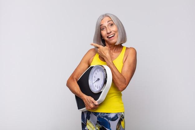 Podekscytowana i zaskoczona kobieta w średnim wieku, wskazująca na bok i do góry, aby skopiować miejsce. koncepcja fitness