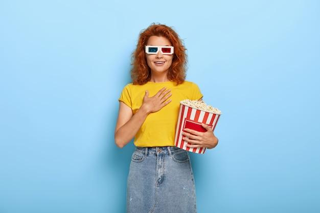 Podekscytowana imbirowa dziewczyna trzyma wiadro z popcornem