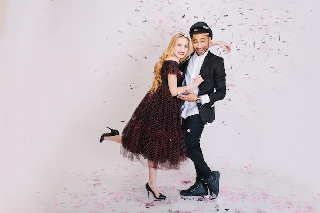 Podekscytowana impreza celebracja zakochanej pary w luksusowych wieczorowych strojach, która bawi się razem. uroczystość, uśmiech, romantyczny, miłość, potliwość.