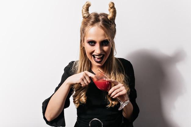 Podekscytowana jasnowłosa dziewczyna pije krew w halloween. oszałamiający wampir w czarnej sukni pozujący na karnawale.