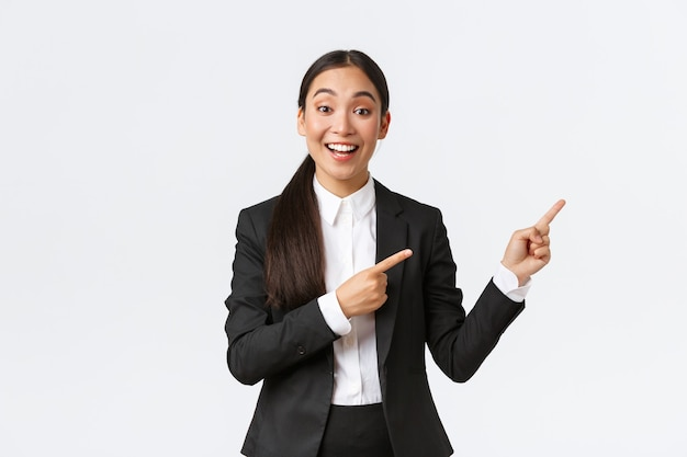 Podekscytowana kobieta azjatycka menedżerka, sprzedawczyni lub agentka nieruchomości pokazująca dom na sprzedaż, wskazująca palcami w prawo, przedsiębiorca przedstawia projekt lub wykres na spotkaniu biznesowym, stojąc w garniturze na białym tle