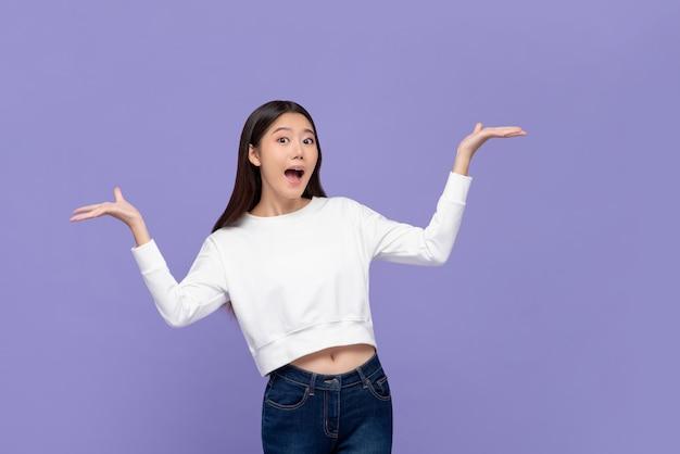 Podekscytowana kobieta azji robi gest prezentacji z otwartymi obiema rękami