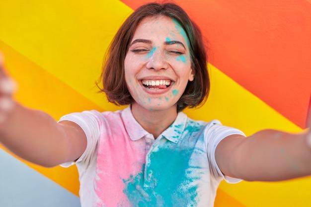 Podekscytowana kobieta biorąc selfie podczas paint party