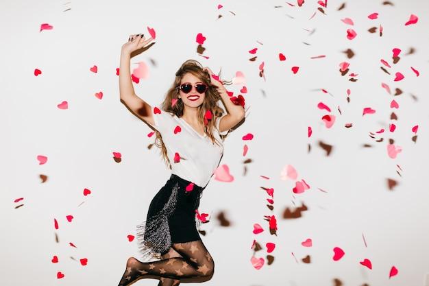 Podekscytowana kobieta boso skacze pod konfetti serca