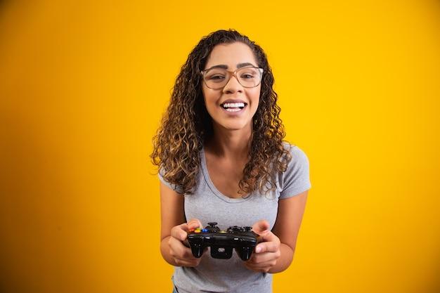 Podekscytowana kobieta, grając w gry wideo na żółtym tle.