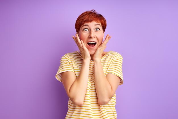 Podekscytowana kobieta jest czymś zaskoczona, stoi krzycząc, wyrażając szczęście, koncepcja ludzkich emocji