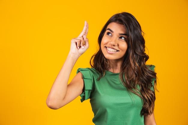 Podekscytowana kobieta palcem wskazującym na wolne miejsce na tekst. pomysł