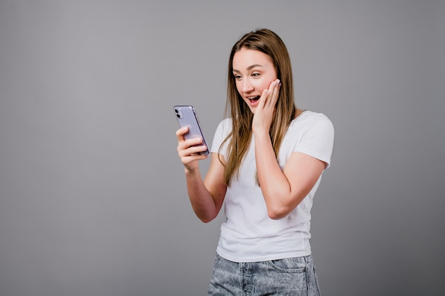 Podekscytowana kobieta patrząc na ekran telefonu na szarym tle