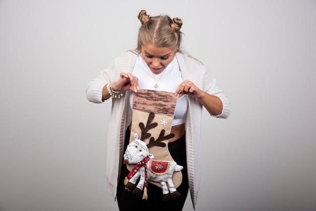 Podekscytowana kobieta, patrząc wewnątrz pończochy świąteczne na szarym tle.