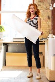 Podekscytowana kobieta. podekscytowana kobieta w pasiastej bluzce, pracująca w biurze wydawniczym, trzymająca rolkę papieru