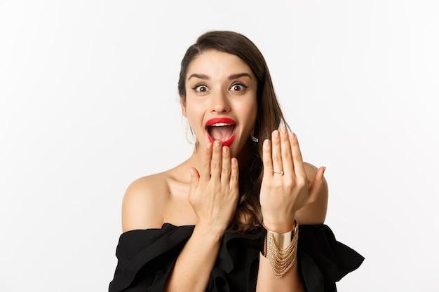 """Podekscytowana kobieta pokazuje pierścionek zaręczynowy po powiedzeniu """"tak"""" propozycji małżeństwa, panna młoda wygląda podekscytowana, stojąc na białym tle."""