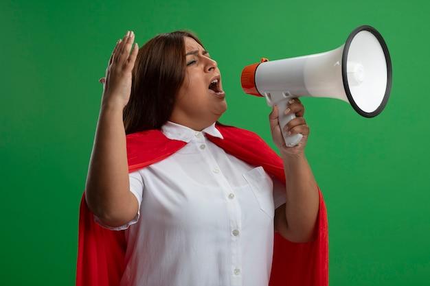 Podekscytowana kobieta superbohatera w średnim wieku, patrząc na bok, mówi na głośniku na białym tle na zielonym tle