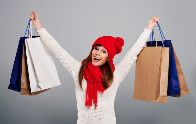 Podekscytowana kobieta trzyma dużo torby na zakupy