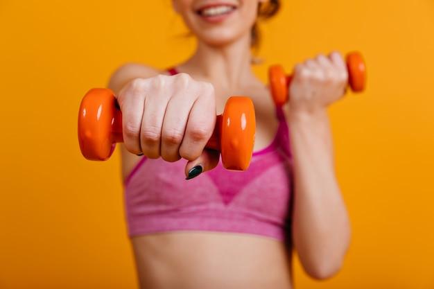 Podekscytowana kobieta trzyma pomarańczowe hantle