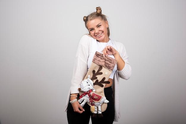 Podekscytowana kobieta trzyma świąteczne skarpety na szarym tle.
