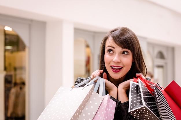 Podekscytowana kobieta trzyma torby na zakupy