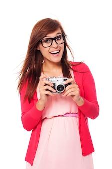 Podekscytowana kobieta trzyma w rękach stary aparat