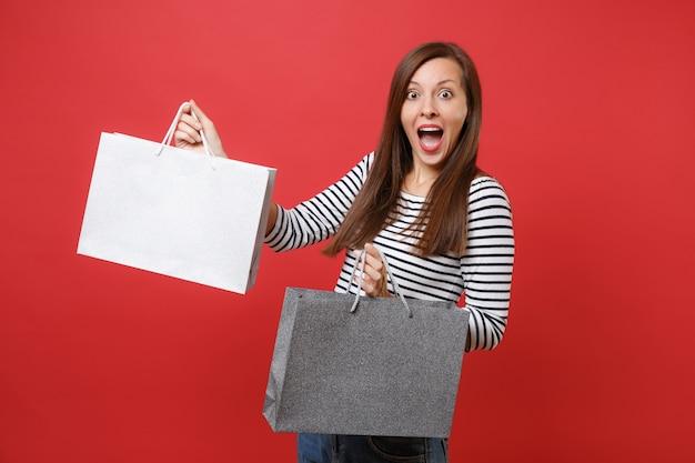 Podekscytowana kobieta trzymająca usta szeroko otwarte, patrząc zdziwiona, trzymająca torby z zakupami po zakupach na białym tle na czerwonym tle. ludzie szczere emocje, koncepcja stylu życia. makieta miejsca na kopię.