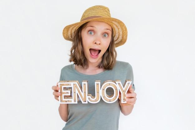 Podekscytowana kobieta w kapeluszu gospodarstwa drewniane słowo cieszyć
