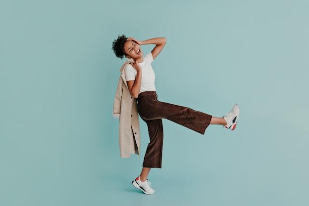Podekscytowana kobieta w spodniach tańczy na turkusowej ścianie
