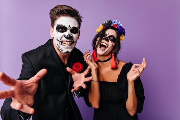 Podekscytowana kobieta w stroju zombie żartuje z chłopakiem. pozytywni młodzi ludzie wygłupiają się w halloween.