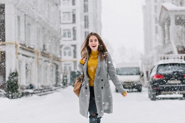 Podekscytowana kobieta w szarym płaszczu i podartych dżinsach idąca drogą w śnieżny dzień. modna kaukaska kobieta spędzająca czas na świeżym powietrzu zimą, zwiedzając miasto.