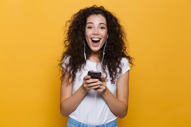 Podekscytowana kobieta w wieku 20 lat z kręconymi włosami, trzymająca smartfona i słuchająca muzyki przez słuchawki izolowane na żółto