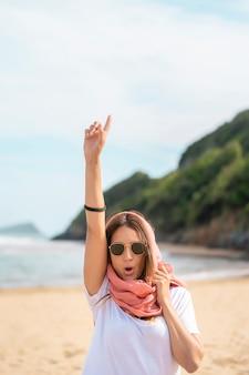 Podekscytowana kobieta wskazująca na plaży okulary przeciwsłoneczne i chusteczkę na głowie