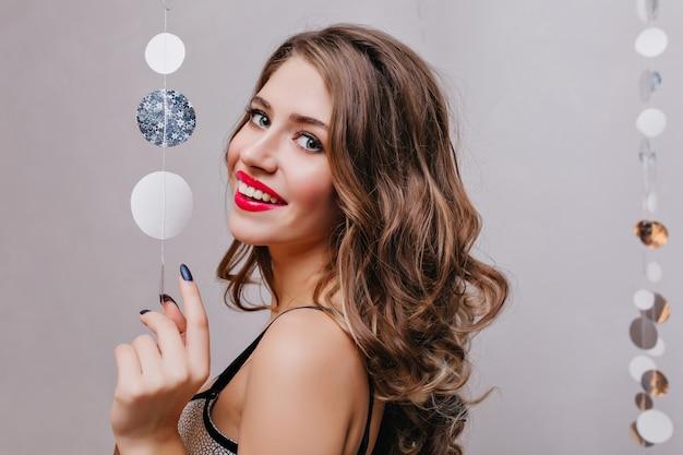 Podekscytowana kobieta z dużymi jasnymi oczami pozuje z radosnym uśmiechem na ciemnej ścianie. kryty zdjęcie radosnej dziewczyny kaukaskiej z brunetką, czekającej na przyjęcie bożonarodzeniowe.