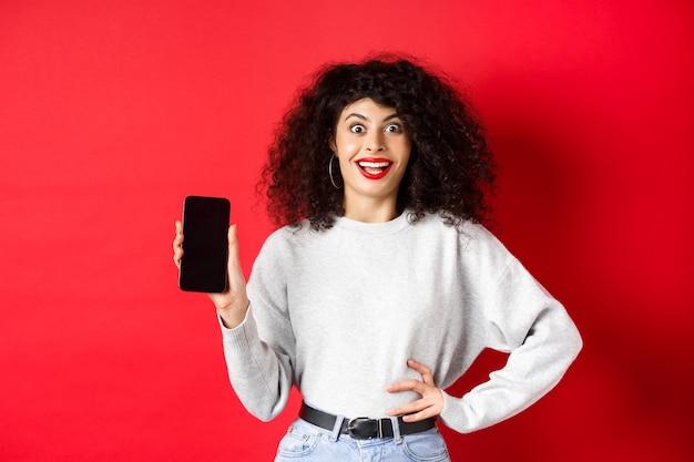 Podekscytowana kobieta z kręconymi włosami i czerwonymi ustami, pokazująca pusty ekran smartfona i krzycząca z radości, stojąca na czerwonym tle.