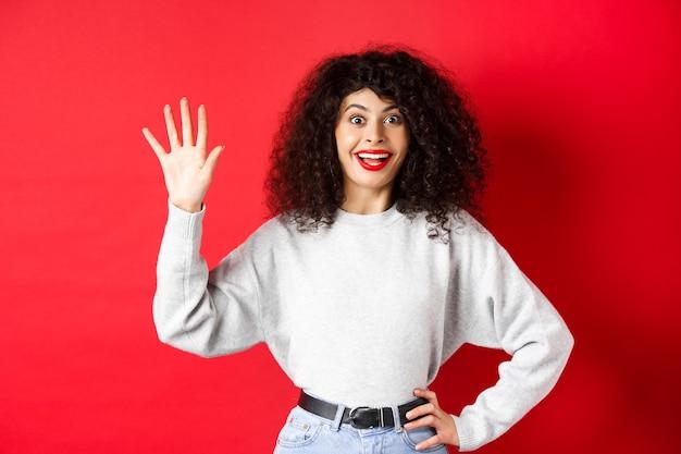 Podekscytowana kobieta z kręconymi włosami pokazująca palcami cyfrę pięć, porządkująca, stojąca na czerwonym tle