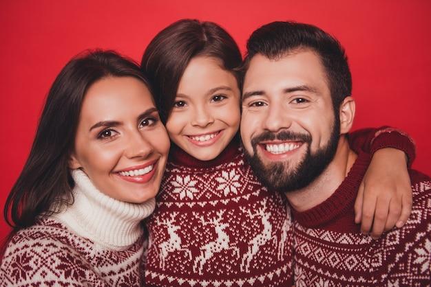Podekscytowana kobieta z mamą i tatą w uroczych, tradycyjnych strojach bożonarodzeniowych z dzianiny