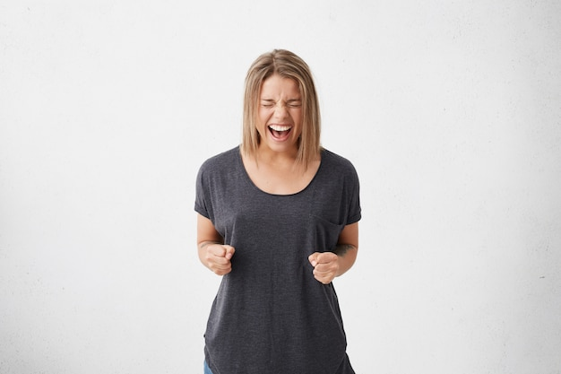 Podekscytowana kobieta z modną fryzurą zamykająca oczy z radości zaciskająca pięści, ciesząc się z triumfu i zwycięstwa. szczęśliwa kobieta krzyczy z pozytywnymi emocjami