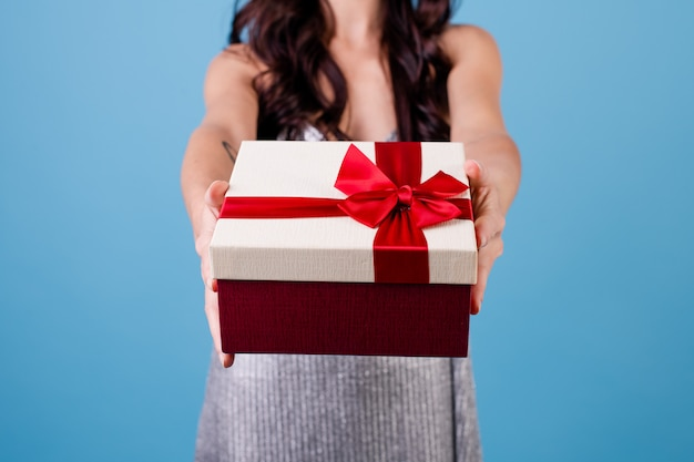 Podekscytowana kobieta z pudełko z czerwoną wstążką na sobie sukienkę na białym tle nad niebieskim