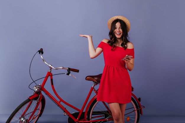 Podekscytowana kobieta z telefonem w ręku, stojąca obok swojego roweru. emocjonalna brunetka dziewczyna w słomkowym kapeluszu pozuje przed rowerem.