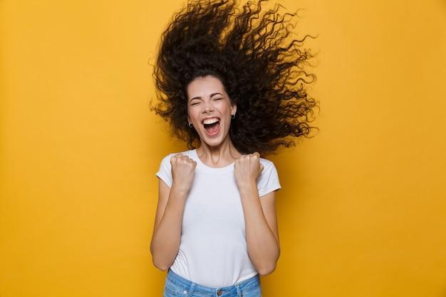 Podekscytowana kobieta z trzęsącymi się włosami, krzycząca i radująca się na żółto