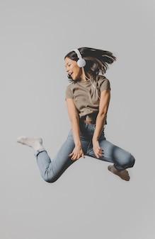 Podekscytowana kobieta ze słuchawkami skacząca w powietrzu