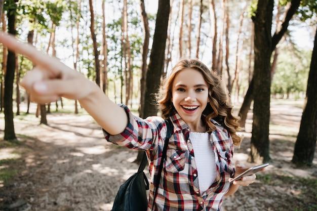 Podekscytowana kręcona dziewczyna szuka właściwej drogi podczas spaceru po lesie. zewnątrz portret emocjonalnej turystki kobiet z plecakiem.