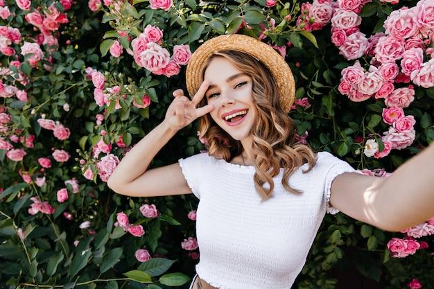Podekscytowana kręcona dziewczyna w letnim stroju co selfie. zewnątrz zdjęcie romantycznej młodej kobiety zabawy w ogrodzie.