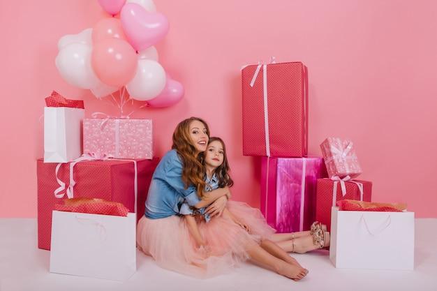 Podekscytowana, kręcona młoda kobieta w kurtce w stylu retro, obejmująca swoją małą bosonogą córkę, otoczona kolorowymi pudełkami. urocza długowłosa dziewczyna siedzi na podłodze z mamą po przyjęciu urodzinowym