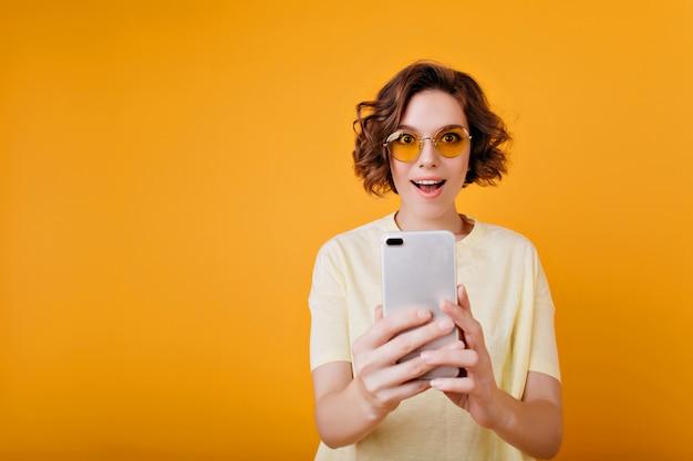 Podekscytowana krótkowłosa kobieta trzyma smartfon na pomarańczowej przestrzeni